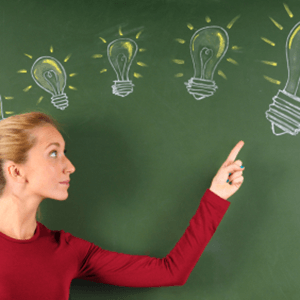 woman pointing to light bulbs drawn on chalkboard